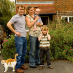 Family and Cat ourside their home